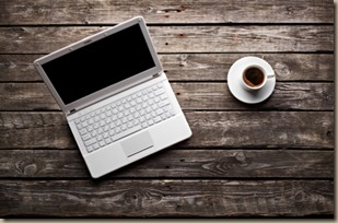 White laptop with coffee cup on old wooden table.